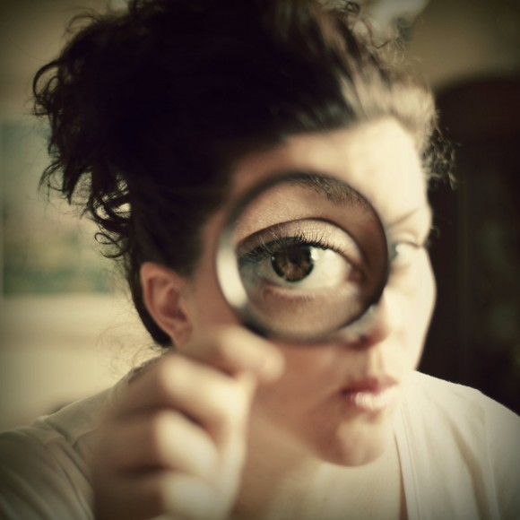 Woman with magnifying glass to her eye